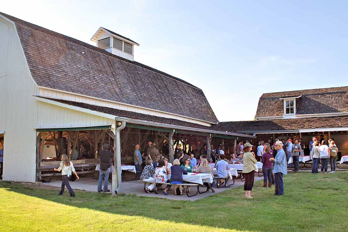 An outdoor get together with plenty of seating two barns and lots of people
