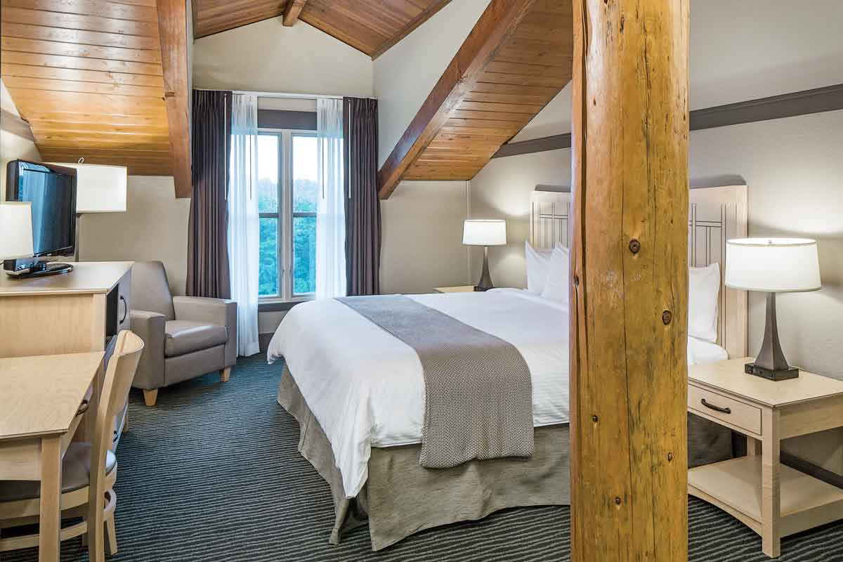 a guest room with stunning views, a bed, two nightstands with lamps, a tv, a desk and a drawer