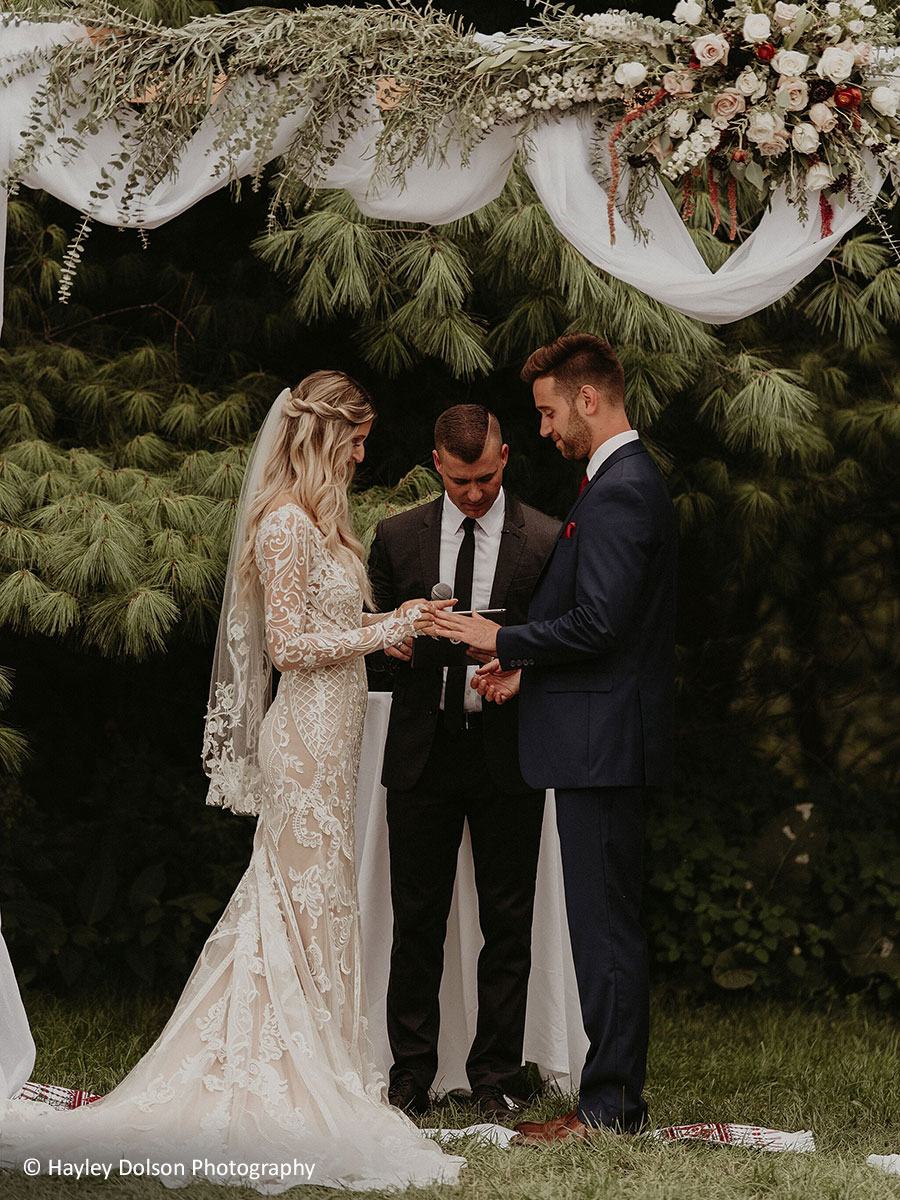 Wedding couple exchanging vows under floral arbor