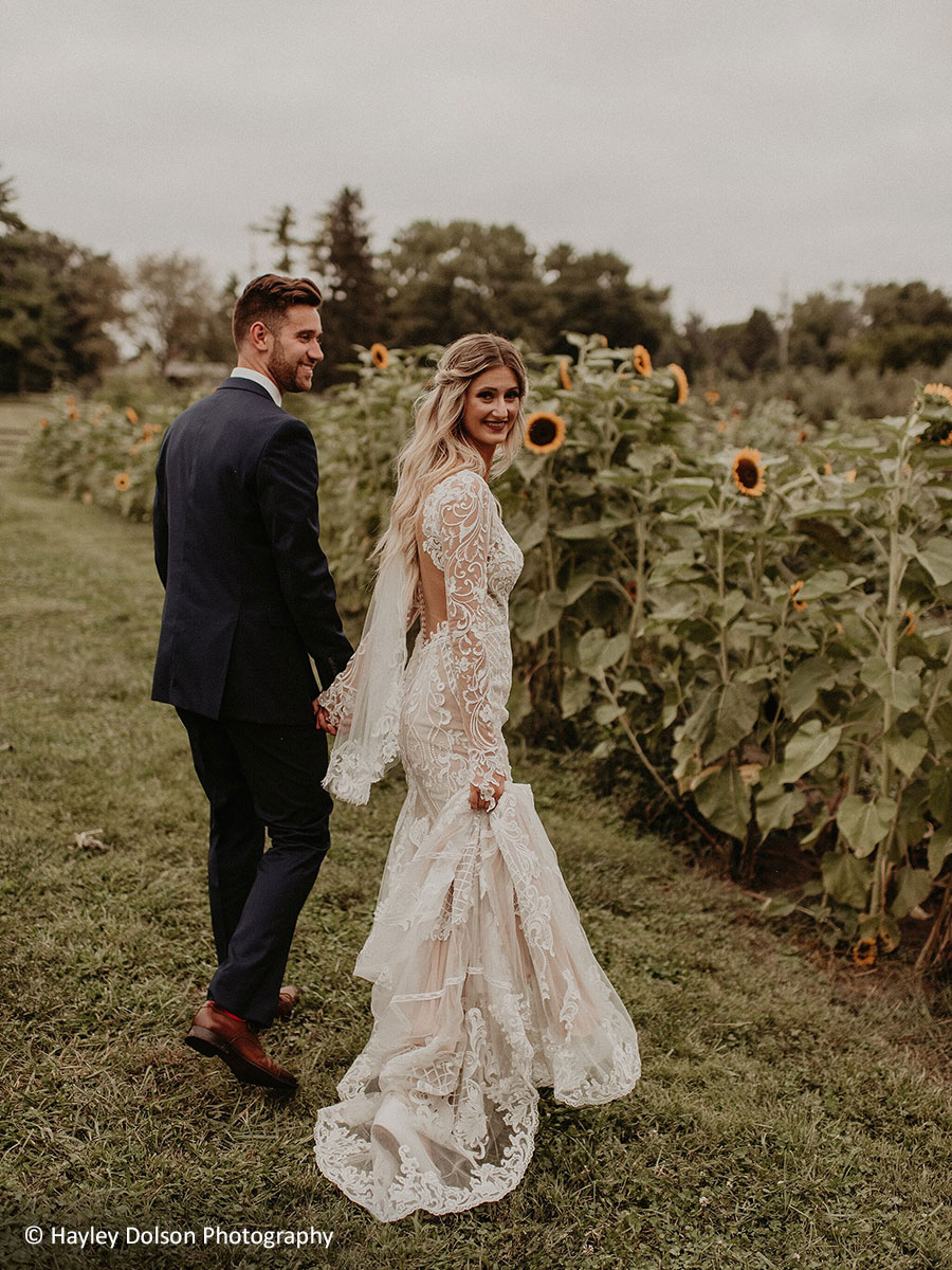 Bride and groom exploring blooming sunflower field