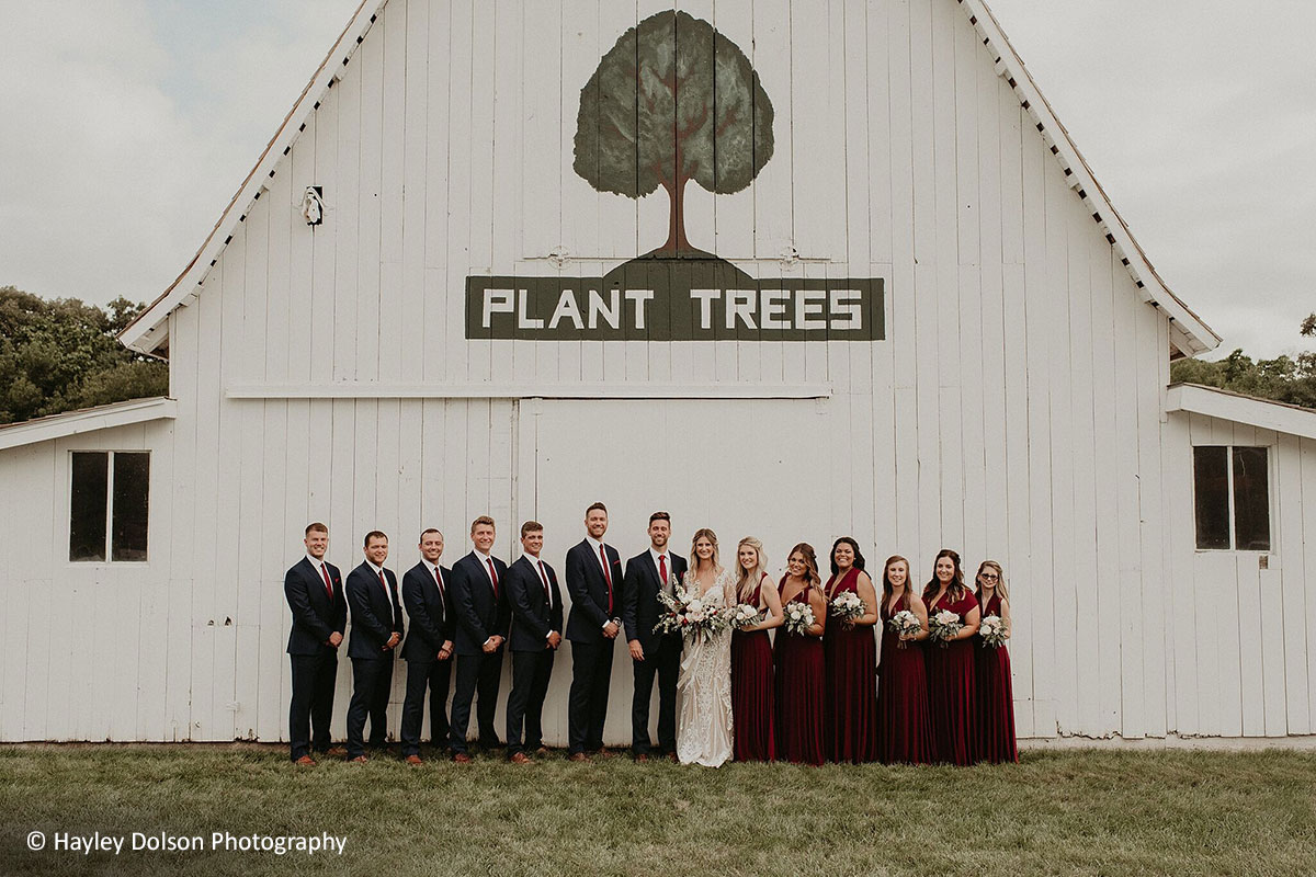 Wedding party in front of Arbor Day Farm barn that says plant trees