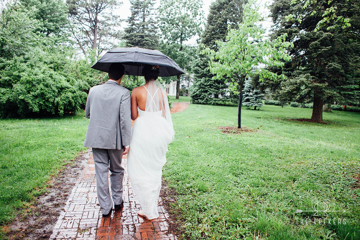 Wedding couple under umbrella walking on a brick sidewalk on way to mansion