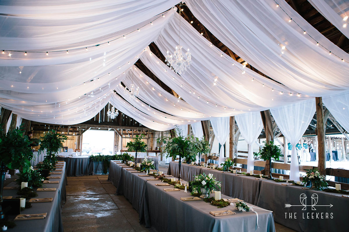 Wide view of reception set up at historic barns with florals, linens & décor
