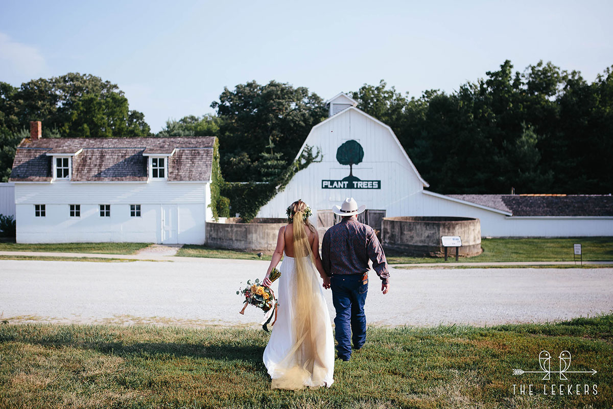 Cowboy and his bride walking toward white barns. Plant trees on barn.