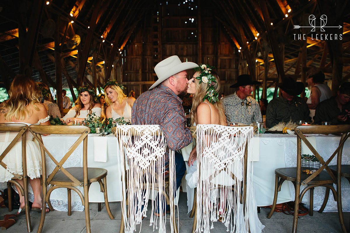 Reception in barn with couple seated at head table and kissing.