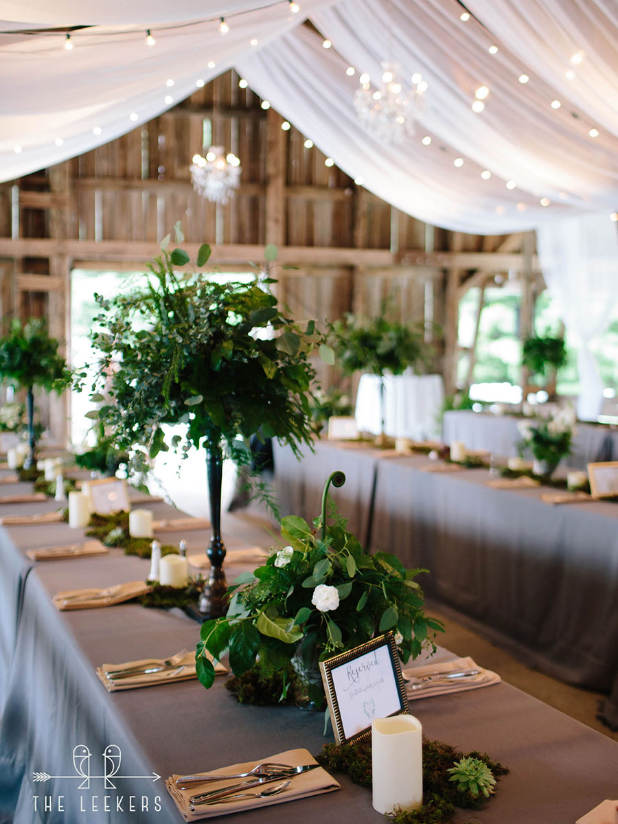 Barns decorated for wedding reception. Tall green florals, white tulle & lights, and gray linens.
