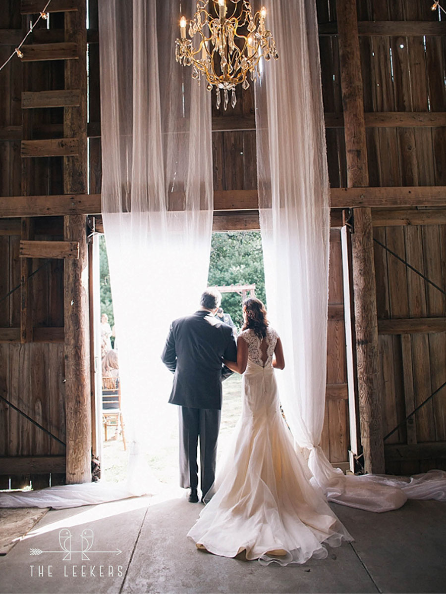 Bride and father from behind as they walk through barn doors to outside ceremony